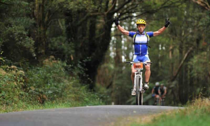 Roger wearing blue bike gear, riding on his bike on a mountain track through trees, hands in the air