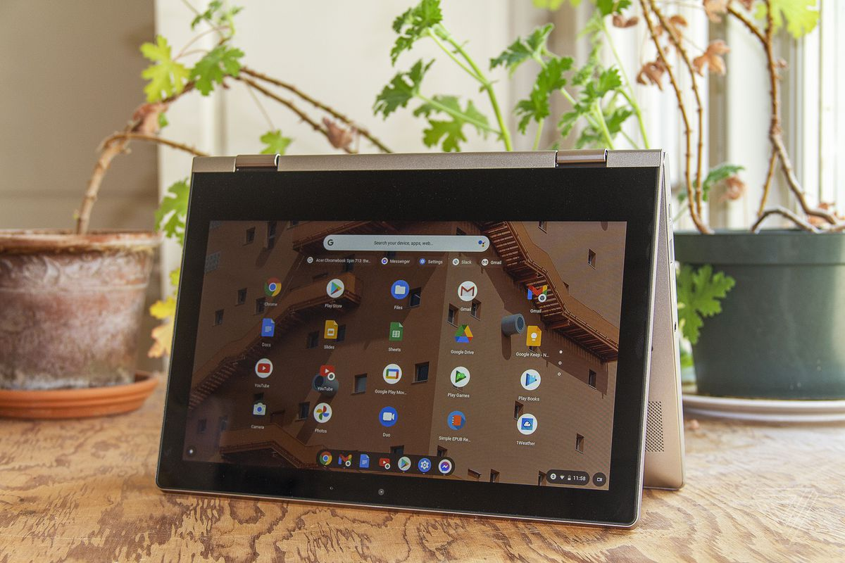 The Lenovo Ideapad Flex 3 Chromebook in tent mode, with the screen facing the camera, angled slightly to the left, sits on a table with two houseplants in the background. The screen displays a grid of Chrome OS app icons.