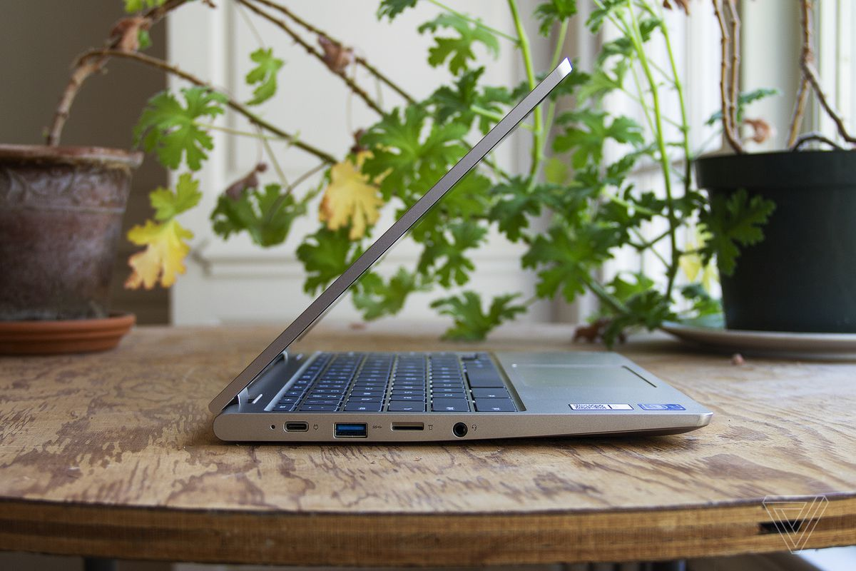 The Lenovo Ideapad Flex 3 Chromebook from the left side, half open on a table in front of two houseplants.
