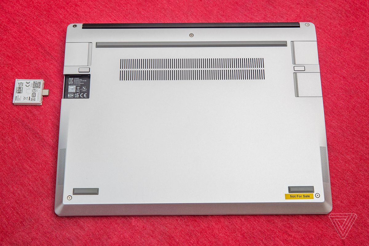 The Framework laptop closed, upside-down on a red tablecloth. One of its four port slots is empty. An expansion card sits beside the empty port, upside-down with its QR code facing up.