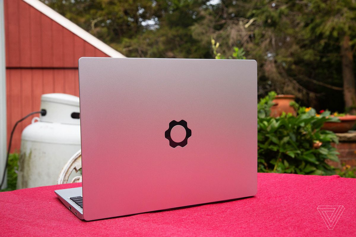 The Framework Laptop in a garden on top of a red tablecloth, facing away from the camera, open, angled to the left.