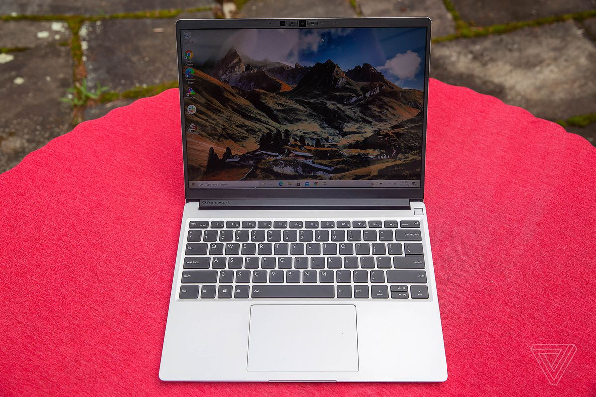 The Framework Laptop outdoors on a red tablecloth, seen from above, open. The screen displays a mountainous landscape.