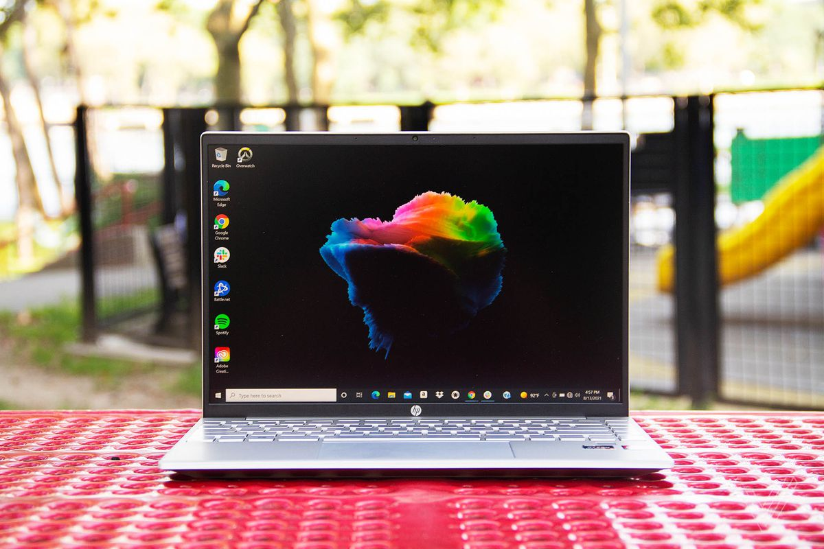 The HP Pavilion Aero 13 open on a red picnic table with a playground in the background. The screen displays a black desktop background with a multicolored cloud in the center.